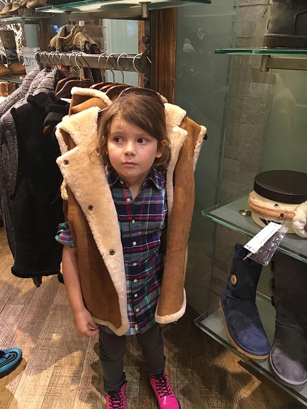 a menina vestiu as roupas no cabide